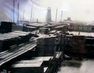 Lumber piles line Thunder Bay River in Alpena c.1885.
