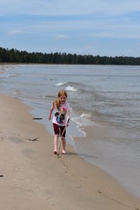 Child plays on the beach at Negwegon State Park