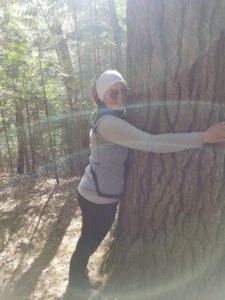 Lisa Kruse hugs a tree.